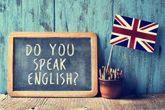 Text do you speak english? in a chalkboard, filtered. A chalkboard with the text do you speak english? written in it, a pot with pencils and the flag of the Stock Image