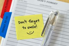 Text don`t forget to smile written on a sticky note over an agen. Da background royalty free stock images