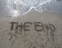 Text THE END written on the sand and the wave that is deleting t. He word can be used for the end of the presentations or at the end of a movie Stock Images