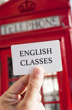 Text english classes in a signboard and a red telephone booth  Royalty Free Stock Images