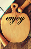 Text enjoy on cutting board Stock Images