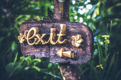 Text EXIT on a wooden plate in a rainforest jungle of tropical Bali island, Indonesia. EXIT inscription in the asian royalty free stock photo