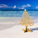 Text för glad jul på den tropiska stranden arkivbild