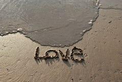 Text för handwritte'förälskelse' på stranden Arkivfoto