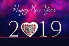Text för lyckligt nytt år och hjärtaprydnad på suddig bakgrund arkivfoton