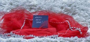 Text för lyckligt nytt år på svart kort med röd tyll och pärlor på wh Fotografering för Bildbyråer