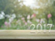 Text för lyckligt nytt år 2017 på trätabellen över suddighetsrosa färger blommar Royaltyfri Fotografi
