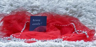 Text för lyckligt nytt år som är skriftlig på franska på svart kort med röd tul Royaltyfri Bild