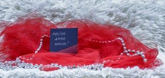 Text för lyckligt nytt år som är skriftlig på italienare på svart kort med röd tu Arkivfoto
