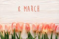 8 text för marsch på rosa tulpan på vit lantlig träbakgrund G arkivfoton