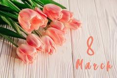 8 text för marsch på rosa tulpan på vit lantlig träbakgrund G Royaltyfria Foton