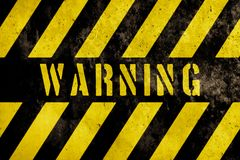 Text för varningstecknet med guling och mörka band som målas över betongväggfasad, texturerar bakgrund royaltyfri fotografi