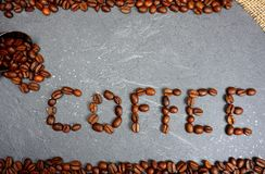 Text from fair trade coffee beans with burlap and spoon at grey kitchen worktop background royalty free stock images