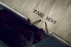 Text fake news written with a typewriter. Closeup of an old typewriter and the text fake news typewritten with it in a yellowish paper Royalty Free Stock Photography