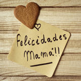 Text felicidades mama, congrats mom in spanish. Closeup of a piece of paper with the text felicidades mama, congrats mom written in spanish and a heart-shaped stock photography