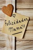 Text felicidades mama, congrats mom in spanish. Closeup of a piece of paper with the text felicidades mama, congrats mom written in spanish and a heart-shaped royalty free stock photography