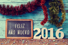 Text feliz ano nuevo 2016, happy new year 2016 in spanish. Tinsel of different colors and a chalkboard with the text feliz ano nuevo, happy new year in spanish stock photos