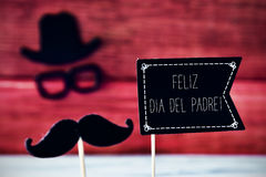 Text feliz dia del padre, happy fathers day in spanish. A black flag-shaped signboard with the text feliz dia del padre, happy fathers day in spanish, and a stock image