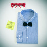 Text feliz dia del padre, happy fathers day in spanish, on a sti. High-angle shot of a table with a pair of eyeglasses, a bow tie and a shirt, and a sticky note Royalty Free Stock Images