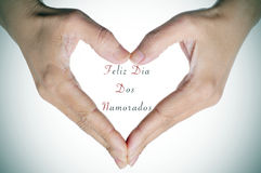 Text Feliz Dia Dos Namorados, in portuguese, for the holiday for. Woman hands forming a heart and the text Feliz Dia Dos Namorados, written in portuguese, to Royalty Free Stock Image