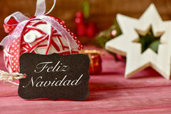 Text feliz navidad, merry christmas in spanish. A black label with the text feliz navidad, merry christmas in spanish, and some different cozy christmas Royalty Free Stock Images