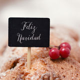 Text feliz navidad, merry christmas in spanish. Closeup of a black signboard with the text feliz navidad, merry christmas in spanish, topping a christmas cake stock images