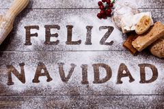 Text feliz navidad, merry christmas in spanish. High-angle shot of a wooden table sprinkled with icing sugar or flour where you can read the text feliz navidad Stock Images