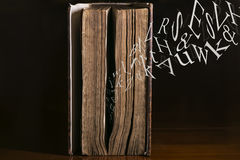 Text Flying out of Old Book. Text Flying out of an old book Royalty Free Stock Photo