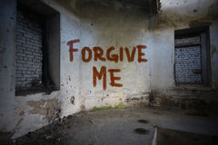 Text forgive me on the dirty old wall in an abandoned  house Stock Images