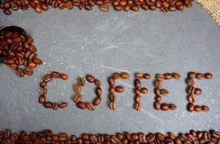 Text från bönor för kaffe för mässahandel med säckväv och skeden på grå kökworktopbakgrund royaltyfria bilder