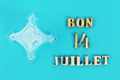 Text in French Good July 14. Miniature of the Eiffel Tower on a blue background. The concept of the holiday The day of the capture Stock Image