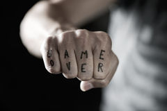 Text game over in the knuckles of a young man Stock Photography