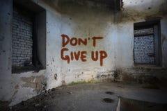 Text geben nicht auf der schmutzigen alten Wand in einem verlassenen Haus auf Stockfoto