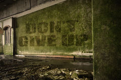 Text geben nicht auf der schmutzigen Wand in einem verlassenen ruinierten Haus auf Lizenzfreies Stockfoto