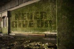 Text geben nie auf der schmutzigen Wand in einem verlassenen ruinierten Haus auf Stockbilder