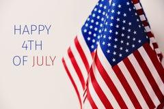 Text glücklich Juli 4. und amerikanische Flaggen Stockbilder