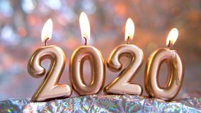Text 2020 golden candles burning. Blurred silver background. Merry christmas and Happy New Year. Selective focus