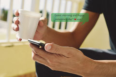 Text good morning and happy valentines day. Closeup of a young caucasian man with a cup of coffee in his hand sending or reading a text message with a smartphone Royalty Free Stock Photo