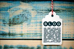 Blog illustrated on tag. Text graphics blog with supporting verbiage illustrated on white tag against grunge blue painted boards Stock Photo