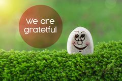 We are grateful. The text we are grateful with stone smile happy face on green moss and sunshine light background stock image