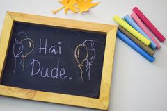 Text hai dude on the chalkboard and colorful chalk,autumn leaf origami. White background.  royalty free stock photography