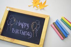 Text Happy Birthday on the chalkboard and colorful chalk,autumn leaf origami. White background