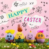 Text happy easter and cute handmade decorated eggs. Text happy easter, as paper cutouts, and some handmade easter eggs, with cute and funny faces, on the grass stock images