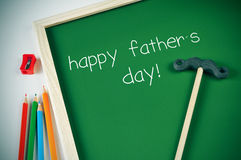 Text happy fathers day in a chalkboard. Some colored pencils of different colors and a framed green chalkboard with the text happy fathers day written in it Stock Images