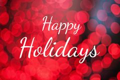 Text Happy Holidays on red lights bokeh background. Christmas and New Year greeting card stock photo