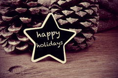 Text happy holidays in a star-shaped blackboard, in black and wh Royalty Free Stock Photo