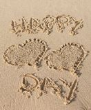 Happy relationship day text on a beach stock photo