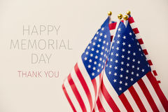 Text happy memorial day and american flags. The text happy memorial day, thank you and some flags of the United States against a beige background Stock Image