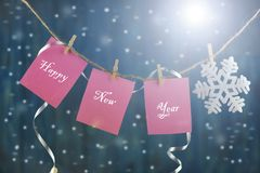 Text Happy New Year. On a piece of paper on a rope with a snowflake and clothespins on a beautiful background Stock Photos