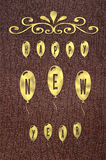 Text Happy New Year written on golden glossy balloons on brown leather background.. Royalty Free Stock Photo